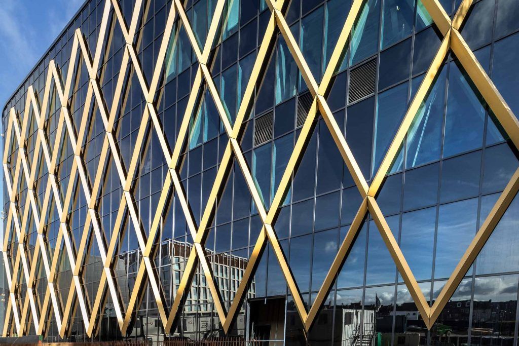 Close up photograph of National Innovation Centre showing gold diagram and dark glazing