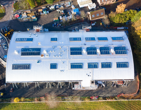 Aerial photograph showing construction site progress of cladding and roofing structure at Velux Glenrothes.