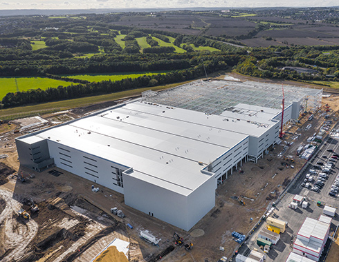 Aerial photography showing construction site progress of construction of warehouse storage facility.