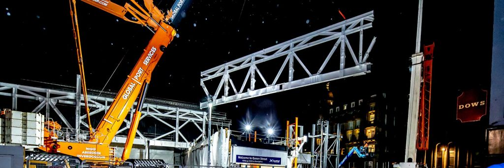 Construction photography rates page showing large orange crange lifting 90te steel structure truss at Queen Street Railway Station Glasgow