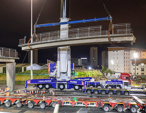 Evening construction photograph of large crane lifting a section of Sighthill M8 Motorway bridge Glasgow