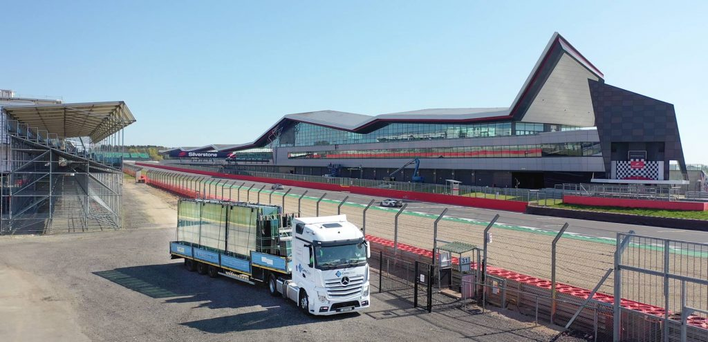 View of SIlverstone Circuit in background with Carey Glass truck in foreground transporting glass for the new bridge linking the new Hilton Garden Inn Silverstone to the trackside Paddock.