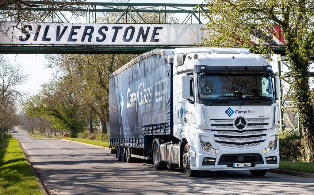 View of SIlverstone Racetrack banner  in background with Carey Glass truck in foreground transporting glass for the new bridge linking the new Hilton Garden Inn Silverstone to the trackside Paddock.