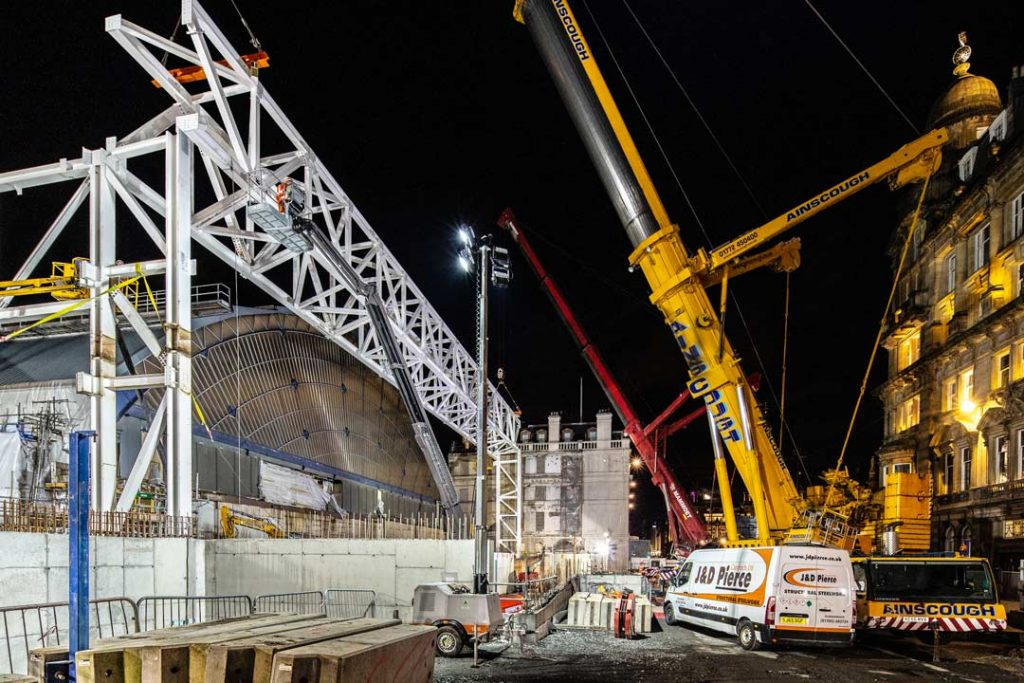 Evening view of construction site involving large steel structure and heavy lift crane at Queen Street Railway Station Glasgow